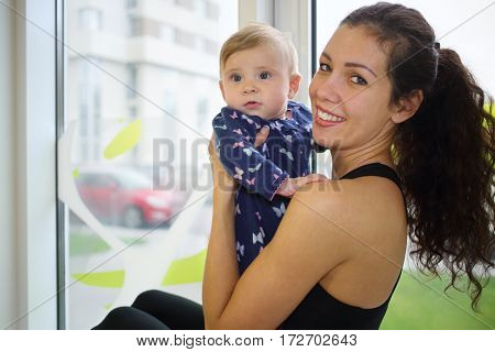 Portrait of happy woman and baby on the windowsill in the gym