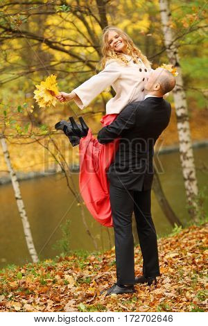 Happy man raises young woman near river in yellow autumn park