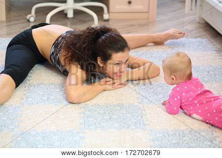 Smiling woman sitting on the splits leaned forward to the baby lying on stomach
