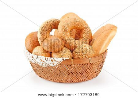 Fresh bread and rolls in wicker basket isolated on white.