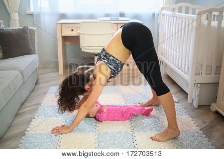 Mother perform exercises while standing on the arms and legs over the baby lying on the floor