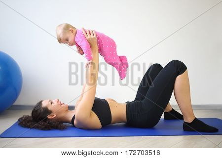 Happy woman lying on her back on the floor lifted up baby in the gym