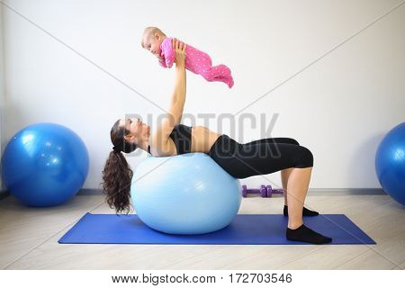 Happy woman lying on the big blue ball on her back lifted up smiling baby in the gym