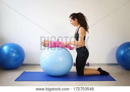 Mother doing gymnastics with a baby on fitball in gym