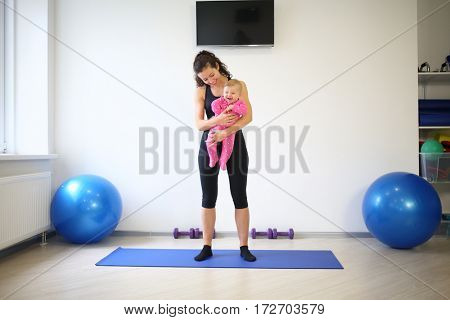Young mother with curly hair in sportswear holding a laughing baby in the gym