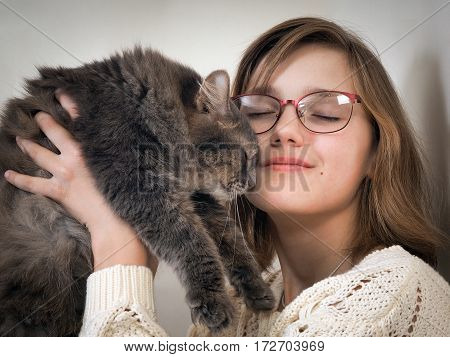 happy girl and a cat. Young girl in glasses and is holding a gray cat