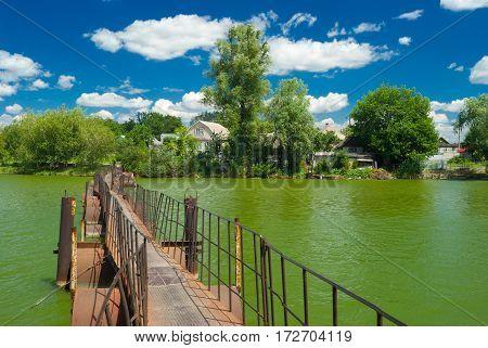 Old pedestrian pontoon-bridge over small green river in Ukrainian village.