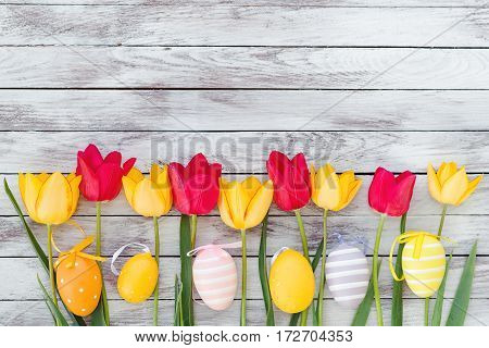 Colorful easter eggs and tulips on the wooden planks.