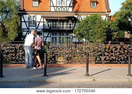 Gdansk Poland - July 19 2014: Couple on the bridge of love. Historical Miller's House on the background.