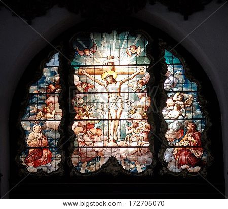 Gdansk Poland - July 19 2014: Crucifixion of Christ shown in an image on a medieval stained glass pane from the St. Mary's Basilica. This Roman Catholic church built in 1379 is the largest brick church in the world.