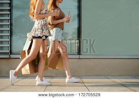 Cropped image of girls with shopping bags walking