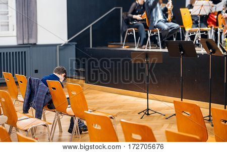Unrecognizable bored kid waiting for the symphonic concert to start by artistic orchestra in Strasbourg France