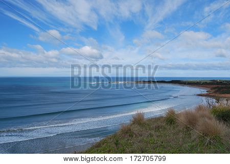 sea with blue sky and clouds across the beach with shrubs