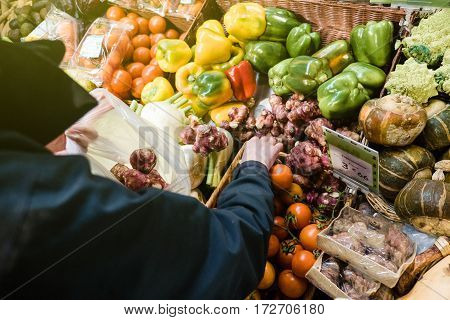 Woman buying at outdoor French market the organic bio fresh Jerusalem artichoke (Helianthus tuberosus) also called sunroot sunchoke earth apple or topinambour is a species of sunflower native to eastern North America and found from eastern Canada and Main