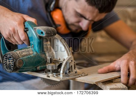 A Man Working With Manual Electric Saw