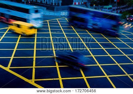 cars driving through yellow no parking area on asphalt streetblue tonedchina.