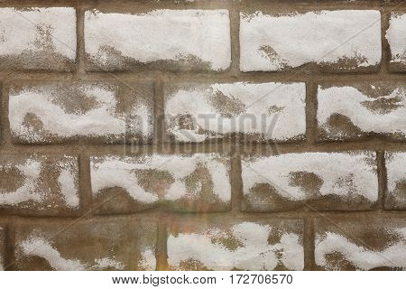 Brown rough brick wall background. Modern wall with decorative stone false bricks, painted texture. Brickwall stucco surface