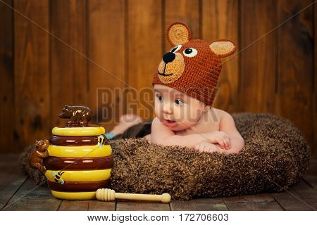 Newborn baby in a knitted cap bears. Surrounded by the teddy bears on the wooden background.