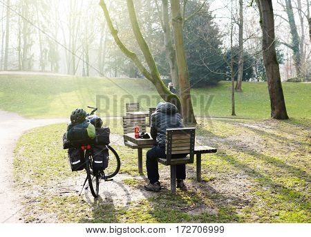 STRASBOURG FRANCE - FEB 12 2017: Single man near parked bicycle drinking beer from metal can in pubic park on a table