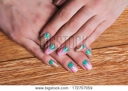 Nail art with bright gold pink and green chevron pattern on wooden background