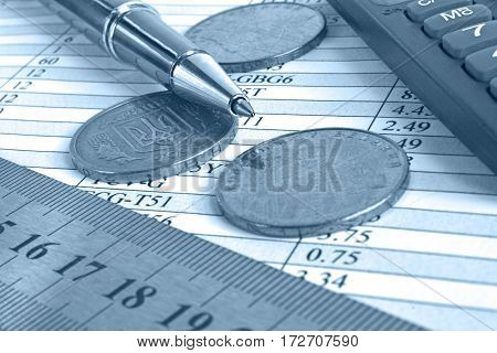 Financial background in blues with money calculator table and pen.