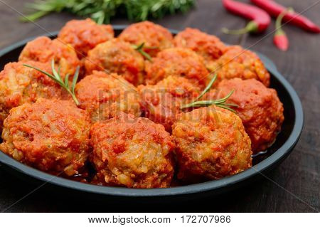 Meat balls in spicy tomato sauce served on a cast iron pan on a dark wooden background. Close up
