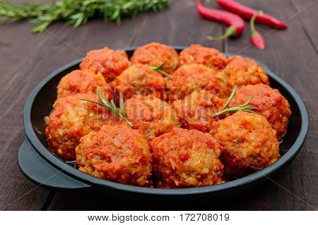 Meat balls in spicy tomato sauce served on a cast iron pan on a dark wooden background.