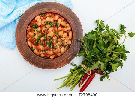 White large beans in sweet and sour tomato sauce in a clay bowl on a light background. Vegetarian cuisine. Lenten meal. The top view