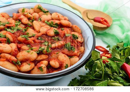 White large beans in sweet and sour tomato sauce in a bowl on a light background. The top view. Vegetarian cuisine. Lenten meal. Close up