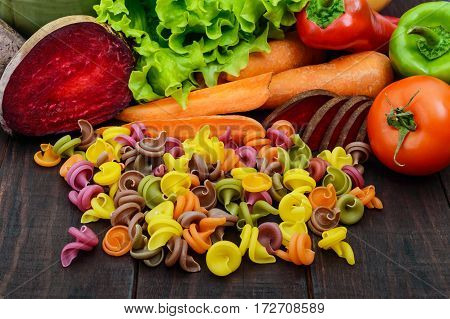 Colorful pasta on a dark rustic wooden table with fresh vegetables (beets greens carrots tomatoes peppers). Healthy food concept.