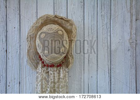 Old lady's hat from point with pearls hangs on the left on old white wooden wall