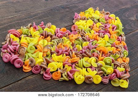 Colorful pasta colored by vegetables (beets greens spinach carrots tomatoes peppers) on a dark wooden table in form of heart . Healthy food concept.