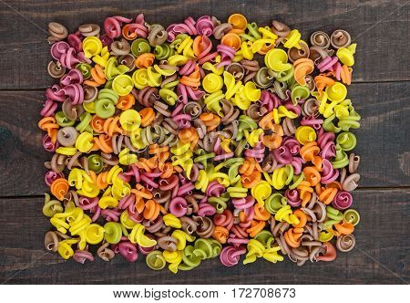 Colorful pasta colored by vegetables (beets greens spinach carrots tomatoes peppers) on a dark wooden table . Healthy food concept. The top view