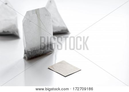 Black tea in teabags with lable on white table background mock up