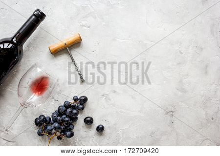 restaurant set with red wine bottle and fresh grape on white stone background top view mock-up