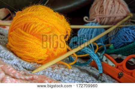 Yellow ball of wool and bamboo spoke for knitting in the foreground. Still life. Horizontal format. Indoors. Color. Photo.