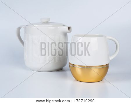 Picture of the white infuser teapot near tea cup decorated witn white and golden colour. Infuser teapot and tea cup on white background.