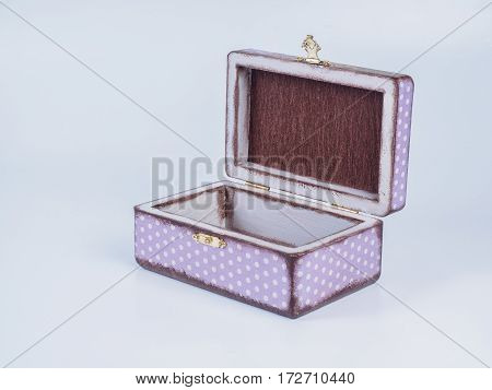 Picture of the opened purple-coloured box for bijouterie on white background. Handmade decoupage jewel box. Side view.