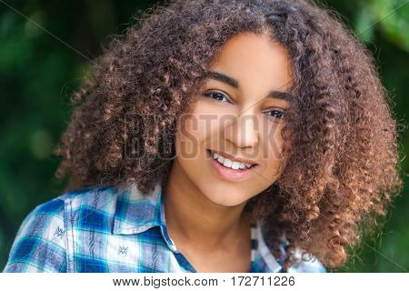 Outdoor portrait of beautiful happy mixed race African American girl teenager female child smiling with perfect teeth
