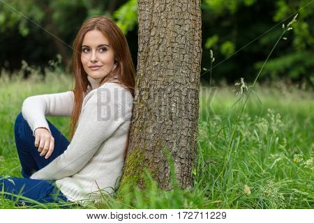 Outdoor portrait of beautiful thoughtful happy girl or young woman with red hair wearing a white jumper sitting & leaning against a tree in the countryside