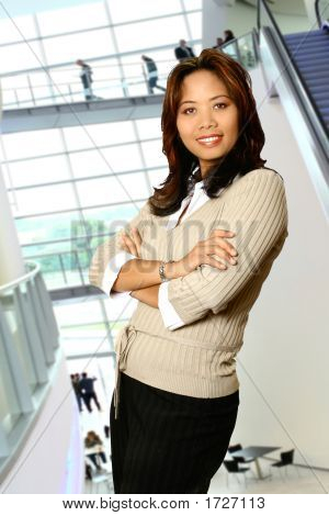 Business Woman Standing, Relaxed, In Corporate Interior