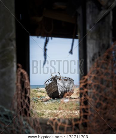 Looking through a broken window at an old abandoned boat