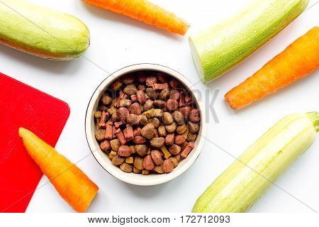 Dry organic dogfood in bowl with fresh carrot and zucchini on white table background top view