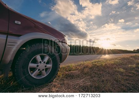 Journey concept. Off road vehicle on the rod at sunset outdoor.