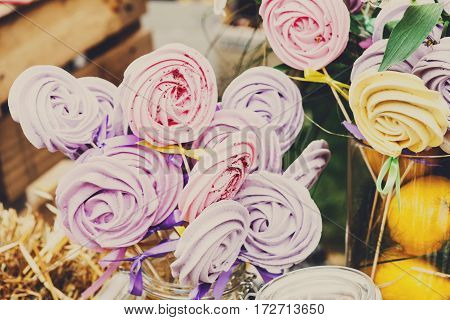 Meringue cakes in rose flower shape on stick assortment on banquet table. Festive holiday catering, serving desserts closeup