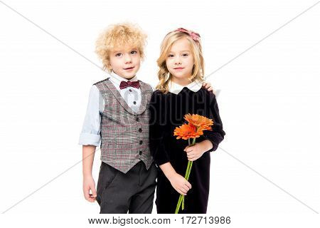 Beautiful little children with flowers looking at camera on white