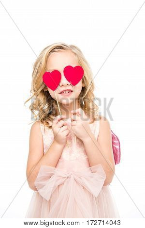 Beautiful girl in pink dress holding red paper hearts on sticks
