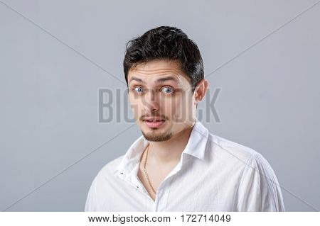 portrait of young attractive surprised brunette male in white shirt on gray background.
