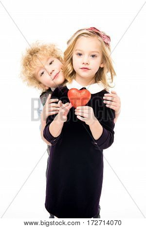 Beautiful little kids standing together and holding red heart sign