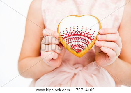 Partial view of girl in pink dress holding heart shaped cookie
